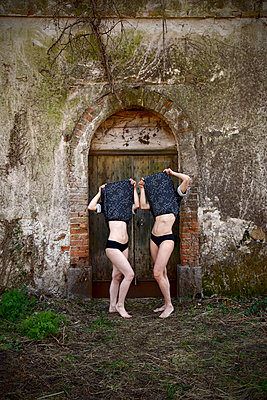 Two women covering their faces with their clothes - p1521m2272088 by Charlotte Zobel