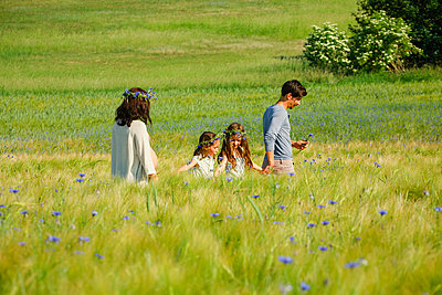 Family walking in sunny, idyllic rural green field with wildflowers - p301m2075660 by Sven Hagolani
