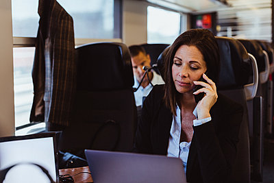Businesswoman talking on smart phone and using laptop while commuting in train - p426m2146142 by Maskot