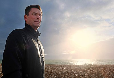 Portrait of mature man looking away from sunlit shingle beach - p429m1102984f by Simon Potter