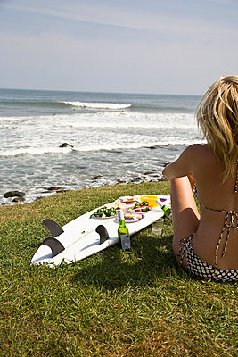USA, Rhode Island, Newport, Young woman in bikini having picnic on surfboard; Judith Point - p442m839858 by Jenny Acheson