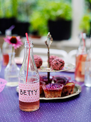 Bottle with lemonade and cupcakes on table - p528m711610f by Anna Kern