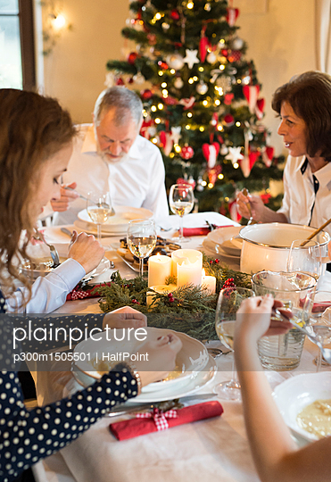 Family dining at Christmas dinner table - p300m1505501 by HalfPoint