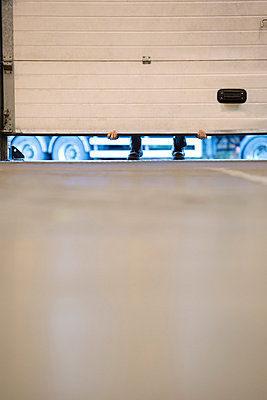 Worker lifting garage door in warehouse - p1023m820030f by Paul Bradbury
