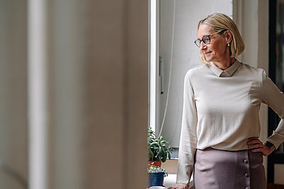 Mature businesswoman looking out of window in office - p300m2156082 by Gustafsson