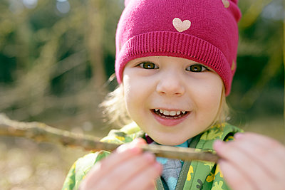 Portrait of smiling little girl with bough in nature - p300m2197385 by Biederbick&Rumpf