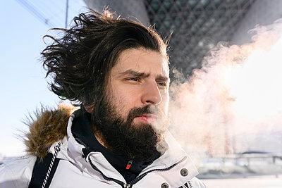 Male hipster exhaling smoke during winter - p300m2251223 by Ekaterina Yakunina
