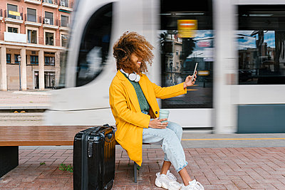 Smiling Afro woman with tousled hair taking selfie through mobile phone while sitting on bench at tram station - p300m2265099 by Ezequiel Giménez