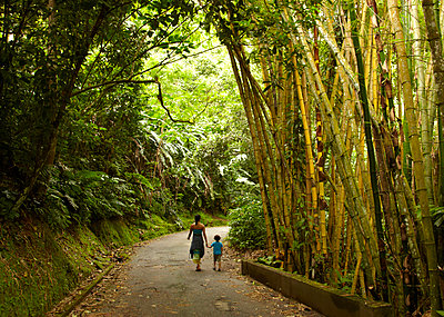 Mixed race mother and child walking on road in jungle - p555m1454279 by Mike Tauber