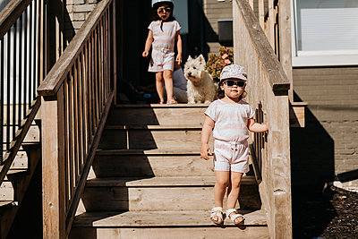 Sisters coming down stairway of house - p924m2153100 by Sara Monika