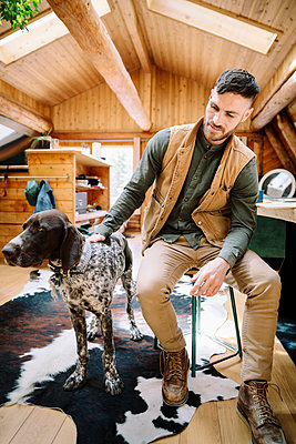 Man with dog in cabin - p1192m2093910 by Hero Images