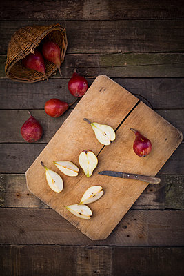 Whole and sliced organic red Clapp's Favourites, wooden board and kitchen knife on dark wood - p300m1068828f by Larissa Veronesi
