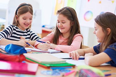 Happy schoolgirls working together in class - p300m1587150 by gpointstudio