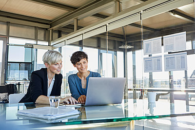 Two smiling businesswomen sharing laptop at desk in office - p300m2081120 by Rainer Berg