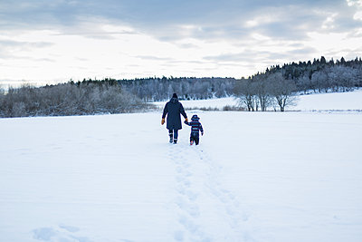 Rear view of mother and child walking in snow - p352m1536599 by Calle Artmark