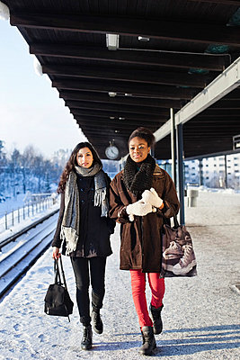 Young female friends in warm clothing walking on station platform - p426m766624f by Maskot