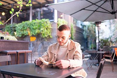Young man reading book at cafe, Milano, Lombardia, Italy - p429m2127483 by Francesco Buttitta