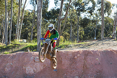 Young male motocross racer jumping down mud hill - p429m983039f by Zero Creatives