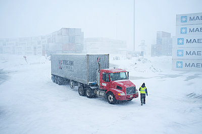 A driver walks to his Horizon Lines truck in the container yard during a snowstorm, Unalaska, Southwest Alaska, USA - p442m1225048 by Dan Parrett