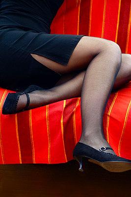 Woman's legs sitting on sofa - p476m1194581 by Ilona Wellmann