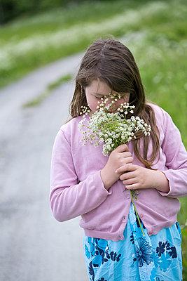 Scandinavia, Sweden, Uppsala, Girl (10-11) smelling bunch of flowers - p528m1075685f by Ewa Ahlin