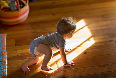 Caucasian baby crawling on floor - p555m1420041 by Marc Romanelli