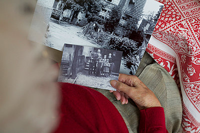 Elderly woman looking at old photographs - p6060608 by Iris Friedrich