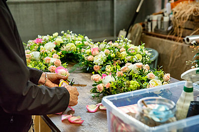 Commercial florist. A woman working on a floral decoration at a workbench.  - p1100m1178285 by Mint Images