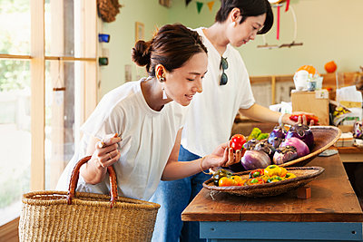 Two smiling Japanese women looking at fresh vegetables in a farm shop. - p1100m2146720 by Mint Images