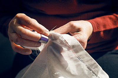 Midsection of woman stitching fabric - p1166m1144727 by Cavan Images