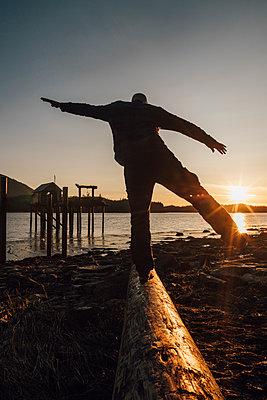 Canada, British Columbia, Port Edward, man balancing on log at sunset - p300m1568041 by Gustafsson
