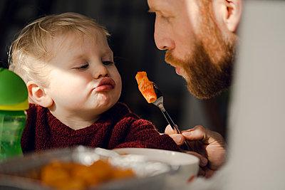 Father feeding his little son with tasty pasta - p300m1581728 von Kniel Synnatzschke