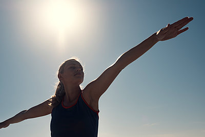 Young woman exercising yoga under blue sky in backlight - p300m2078590 by André Babiak