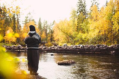 Woman fishing in river - p312m2091378 by Matilda Holmqvist