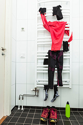 Sports clothing hanging on racks in bathroom - p426m1017971f by Katja Kircher