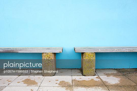 Zwei hölzerne Bänke vor einer blauen Wand - p1057m1586853 von Stephen Shepherd