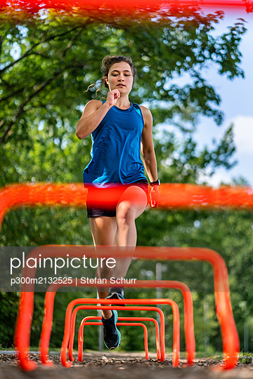 Young woman jumping over hurdles on a woodchip trail - p300m2132525 by Stefan Schurr