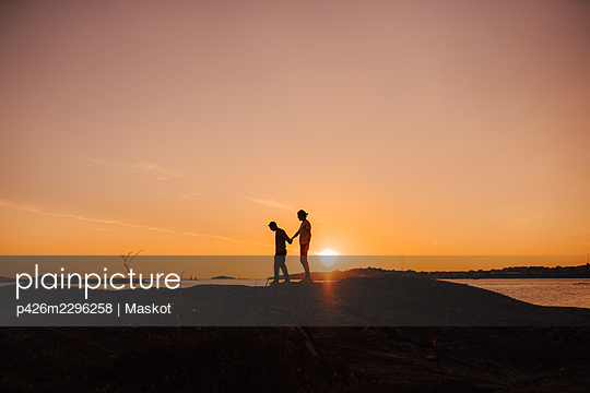 Male friends holding hands while walking at lakeshore during sunset - p426m2296258 by Maskot