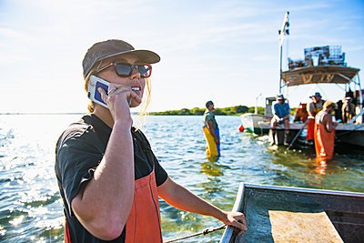Woman on Phone while working on the water in aquaculture oyster farm - p1166m2268901 by Cavan Images