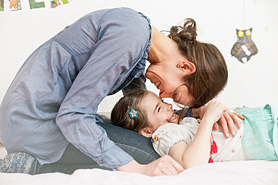 Mother cuddling her little daughter at home - p300m1188400 by Mareen Fischinger