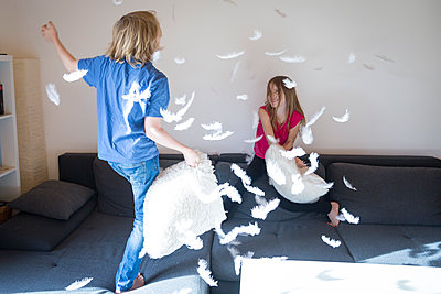 Pillow fight between brother and sister at home - p300m1205093 by Sandra Roesch