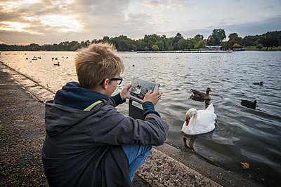 UK, London, boy photographing water birds at Hyde Park with his digital tablet - p300m975296f by Andreas Pacek