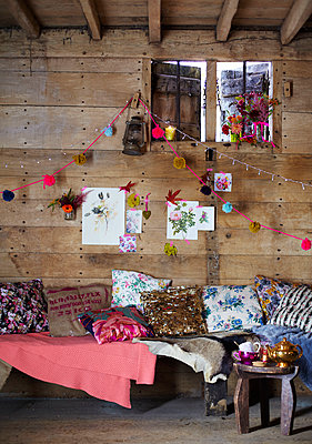 Assorted cushions on bench seat below window in rustic wood cabin in Autumn  UK - p349m2167842 by Sussie Bell