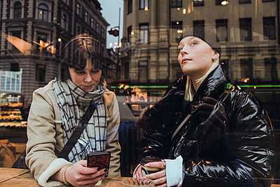 Thoughtful young woman looking through glass window while friend using mobile phone in cafe during winter - p426m2088918 by Maskot