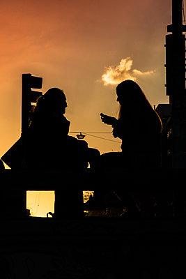 Women sitting outdoors - p623m2186524 by Pablo Camacho