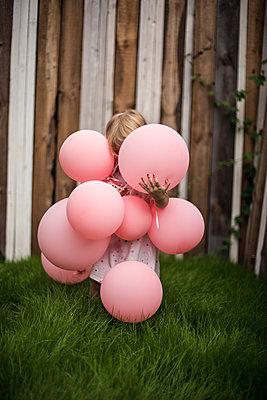 Kind hinter Luftballons versteckt  - p941m1559821 by lina gruen