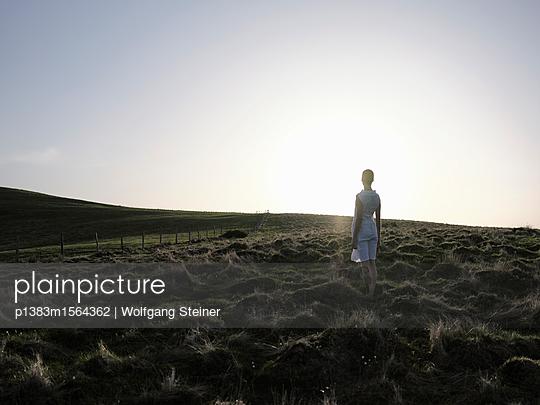 Frau im weißen Kleid steht im Gegenlicht auf einer Wiese - p1383m1564362 von Wolfgang Steiner
