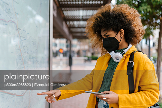 Afro woman with mobile phone looking at map during COVID-19 - p300m2265820 by Ezequiel Giménez