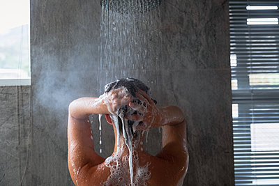 Young woman washing her hair in a shower in a modern bathroom - p1315m2130786 by Wavebreak