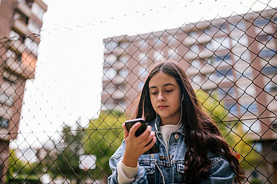 Low angle view of teenage girl using smart phone while standing against chainlink fence - p300m2198358 by LUPE RODRIGUEZ
